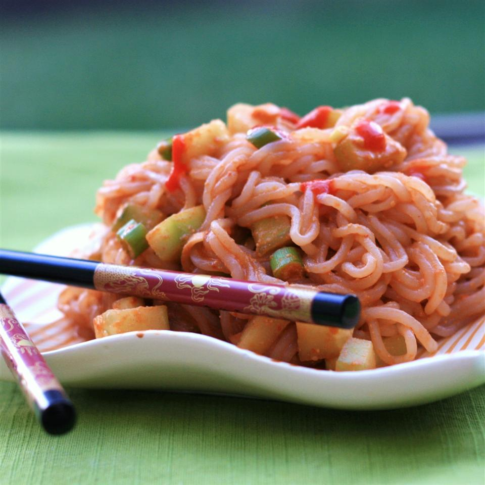 noodles with peanut sauce on white plate with chopsticks