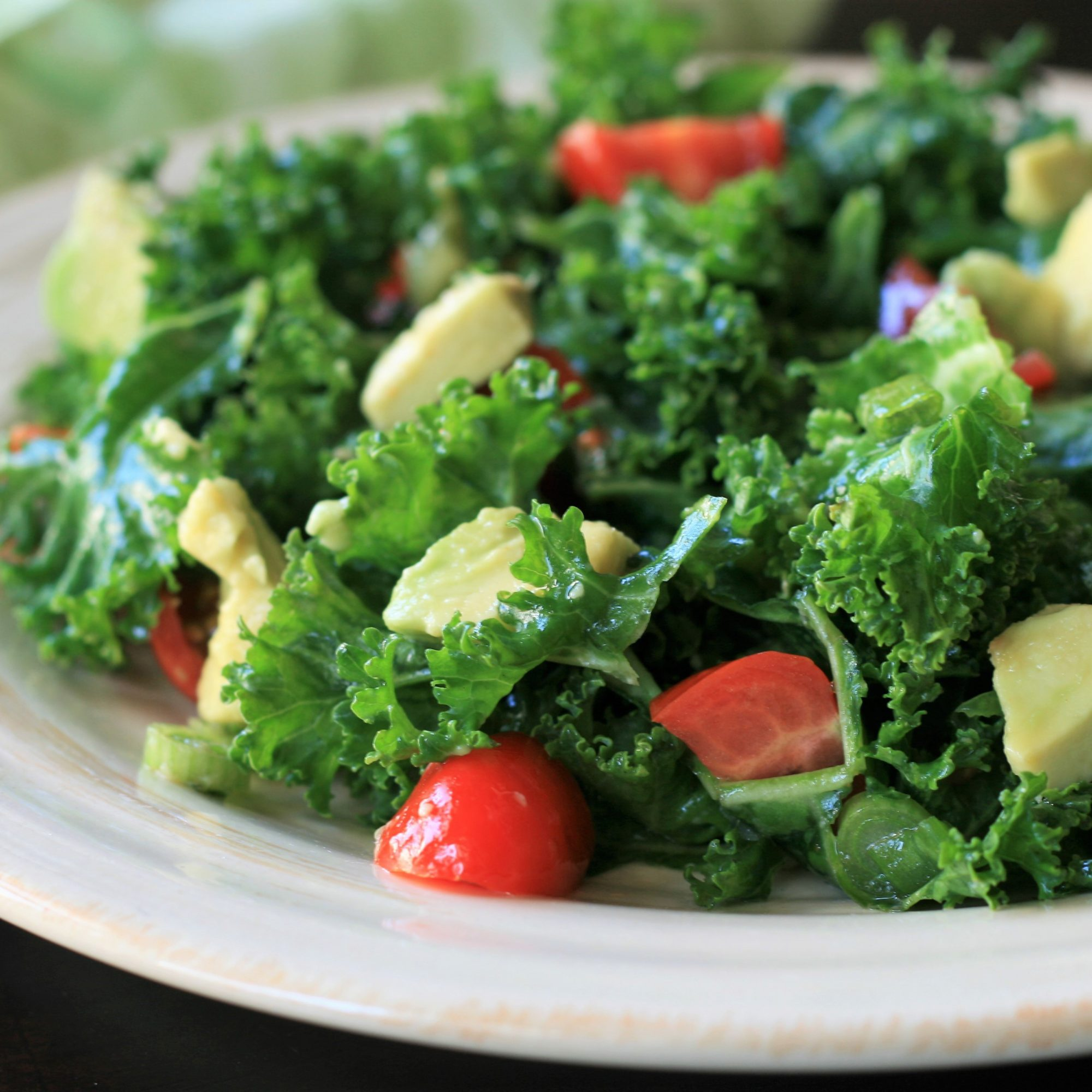 Kale Salad with Avocado on a white plate