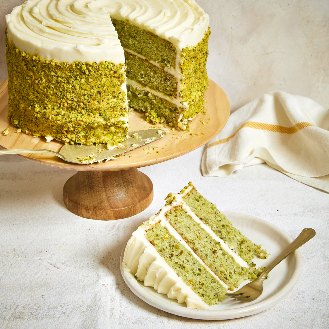 Beautiful layered pistachio cake on a wooden cake stand with a slice out and plated.