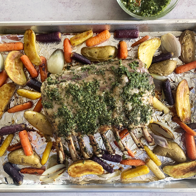 Roasted half rack of lamb resting on a sheet tray with roasted potatoes, carrots, and onions
