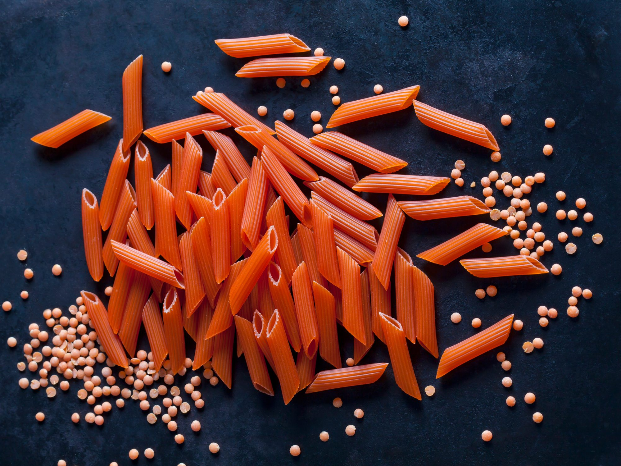Red Penne Rigate and red lentils on dark ground