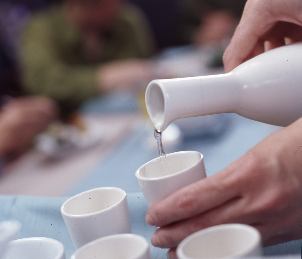 pouring sake into white cups
