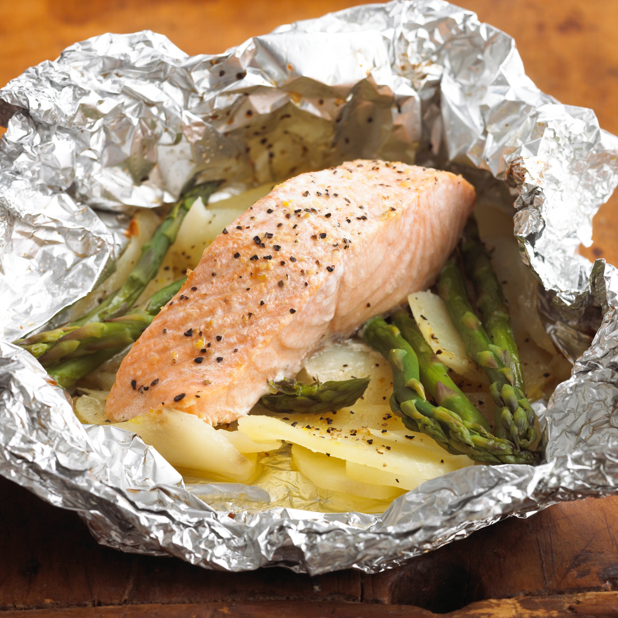 salmon fillet in foil with potatoes and asparagus