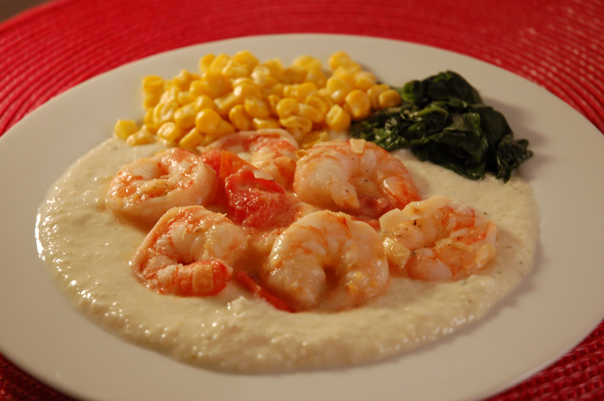 """How Lowcountry can you go? Shelled shrimp are sauteed with diced tomato in olive oil and butter and served over garlic cheese grits. """"This is the best and easiest shrimp and grits recipe!"""" says Carol. """"I have also added andouille sausage sometimes for a different flavor excellent."""""""