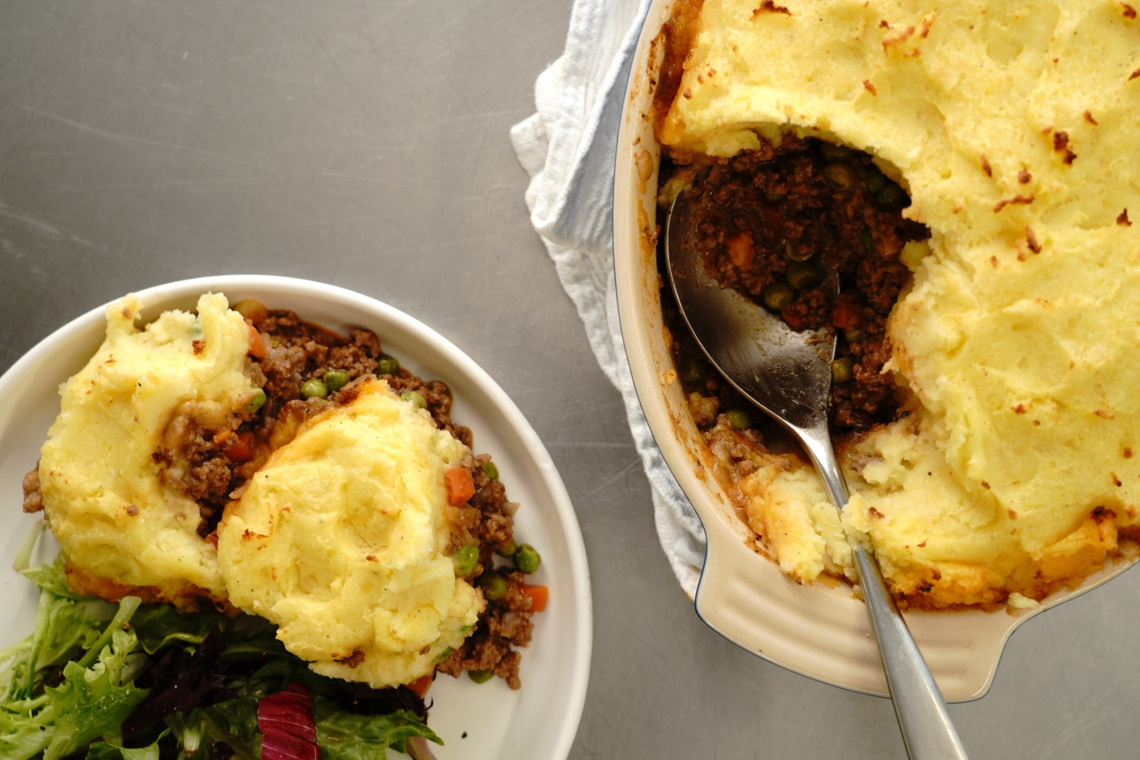 overhead shot of shepherd's pie in a casserole dish and served on a plate with salad