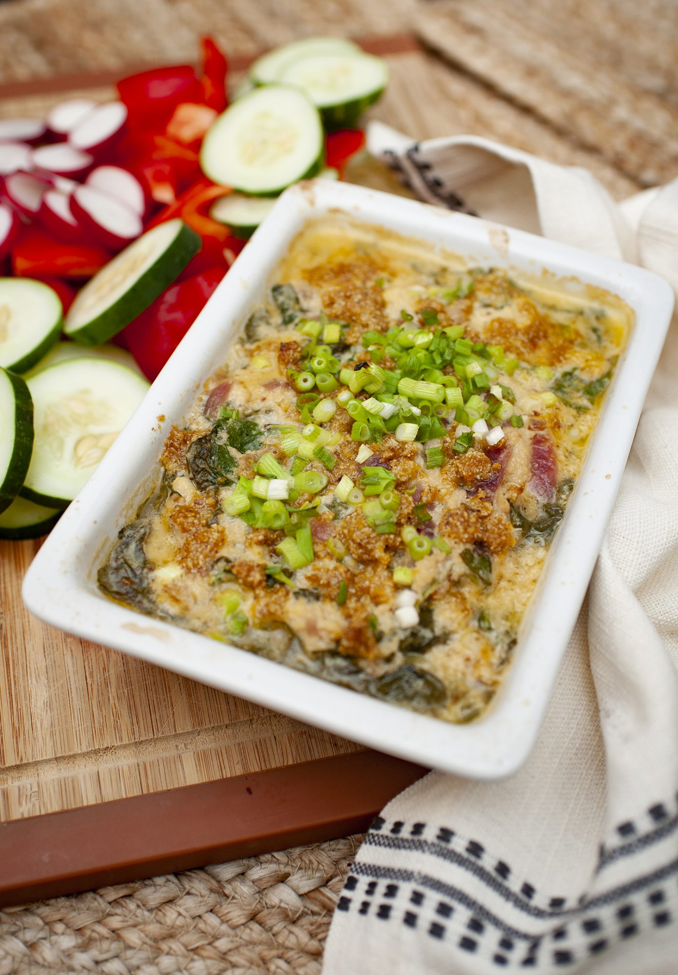 crab dip with spinach and green onion in square dish