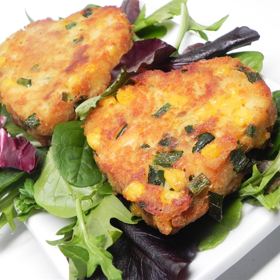 crab cakes with peppers and corn in side over bed of lettuce