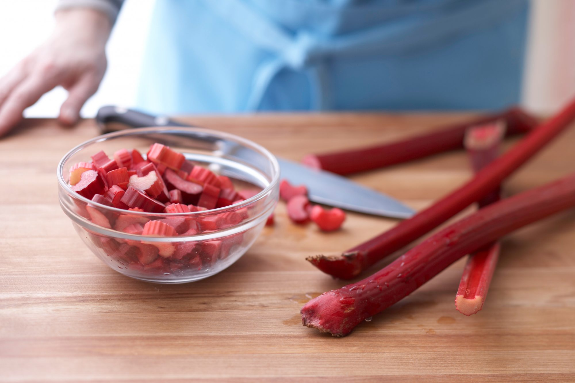 rhubarb stalks with knife on cutting board and cut pieces in bowl