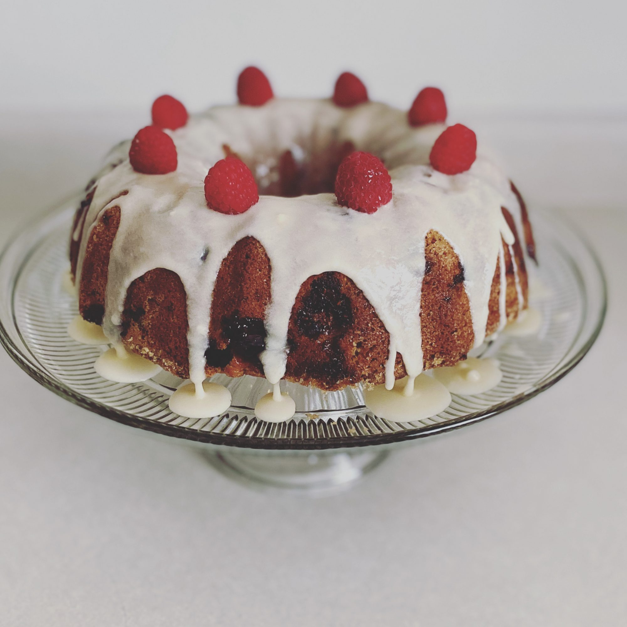 blueberry pound cake with icing glaze and raspberry topping