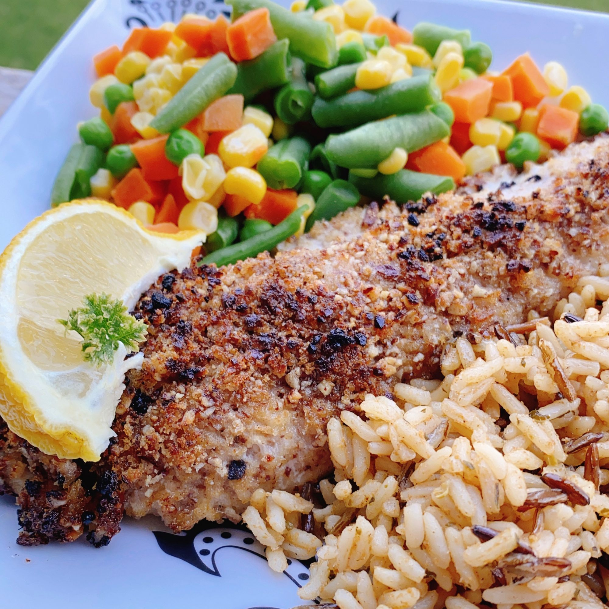 Pecan-Crusted Rockfish with Old Bay on a blue plate