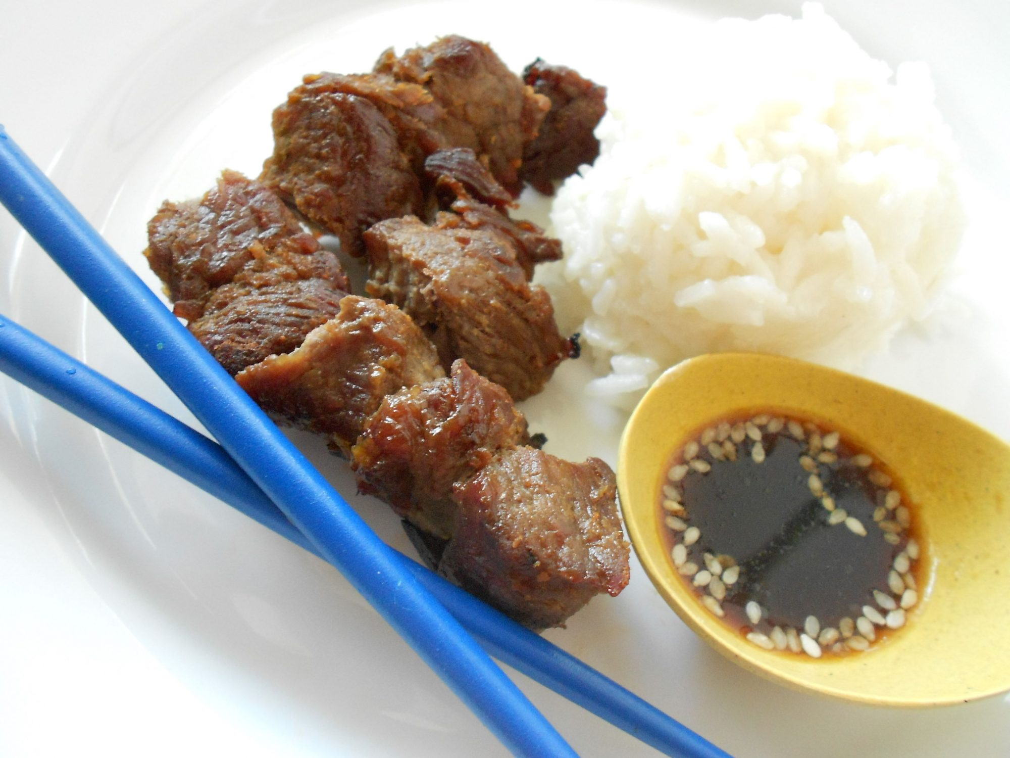 Thin slices of sirloin steak are marinated in a sweet and savory combination of mirin and soy, rolled around pieces of green onion, and broiled or grilled.