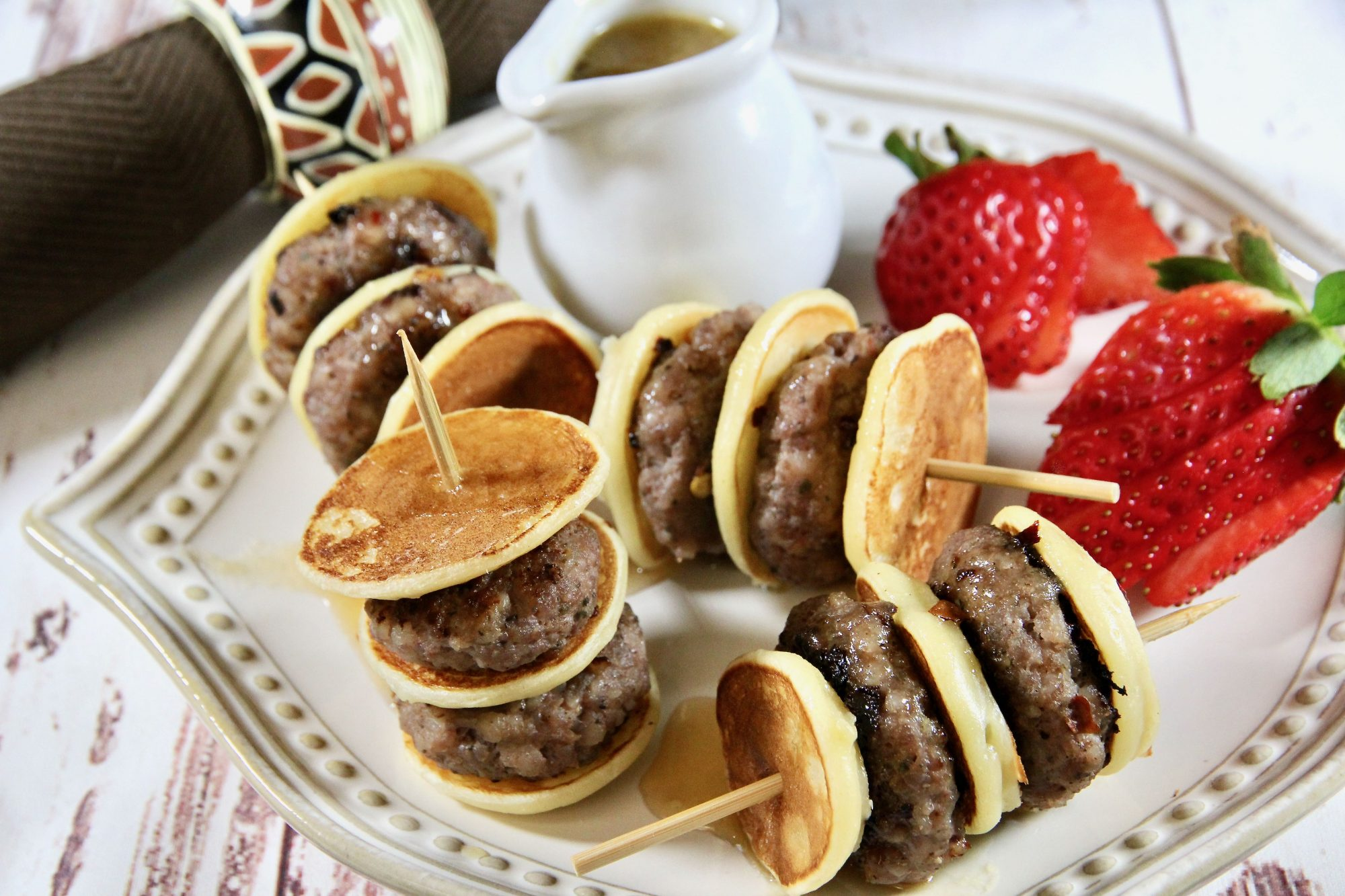 mini pancakes threaded onto skewers with mini sausage patties and served with fruit and syrup