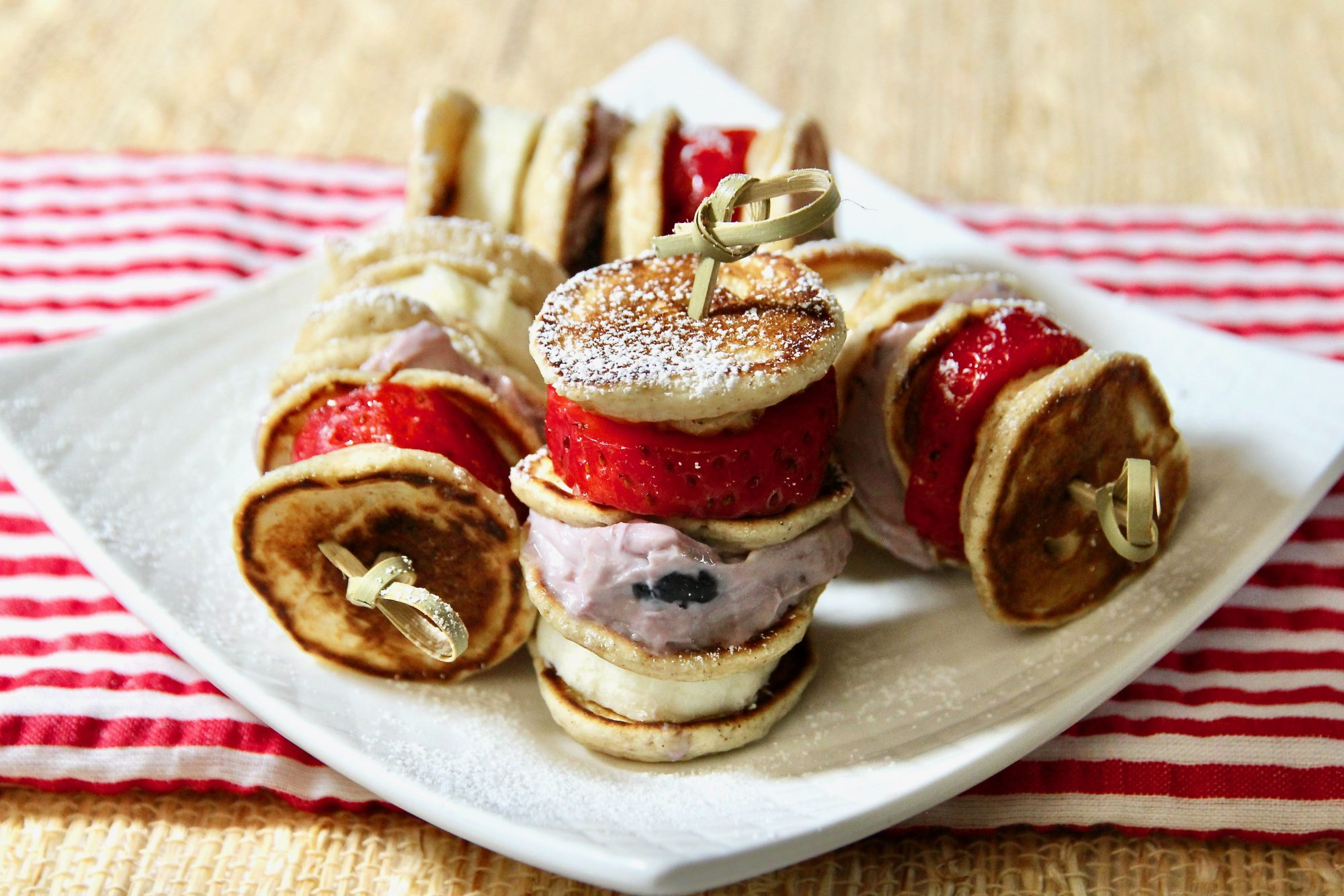 bite-size pancakes threaded on skewers with sliced bananas, fruited cream cheese, and sliced strawberries