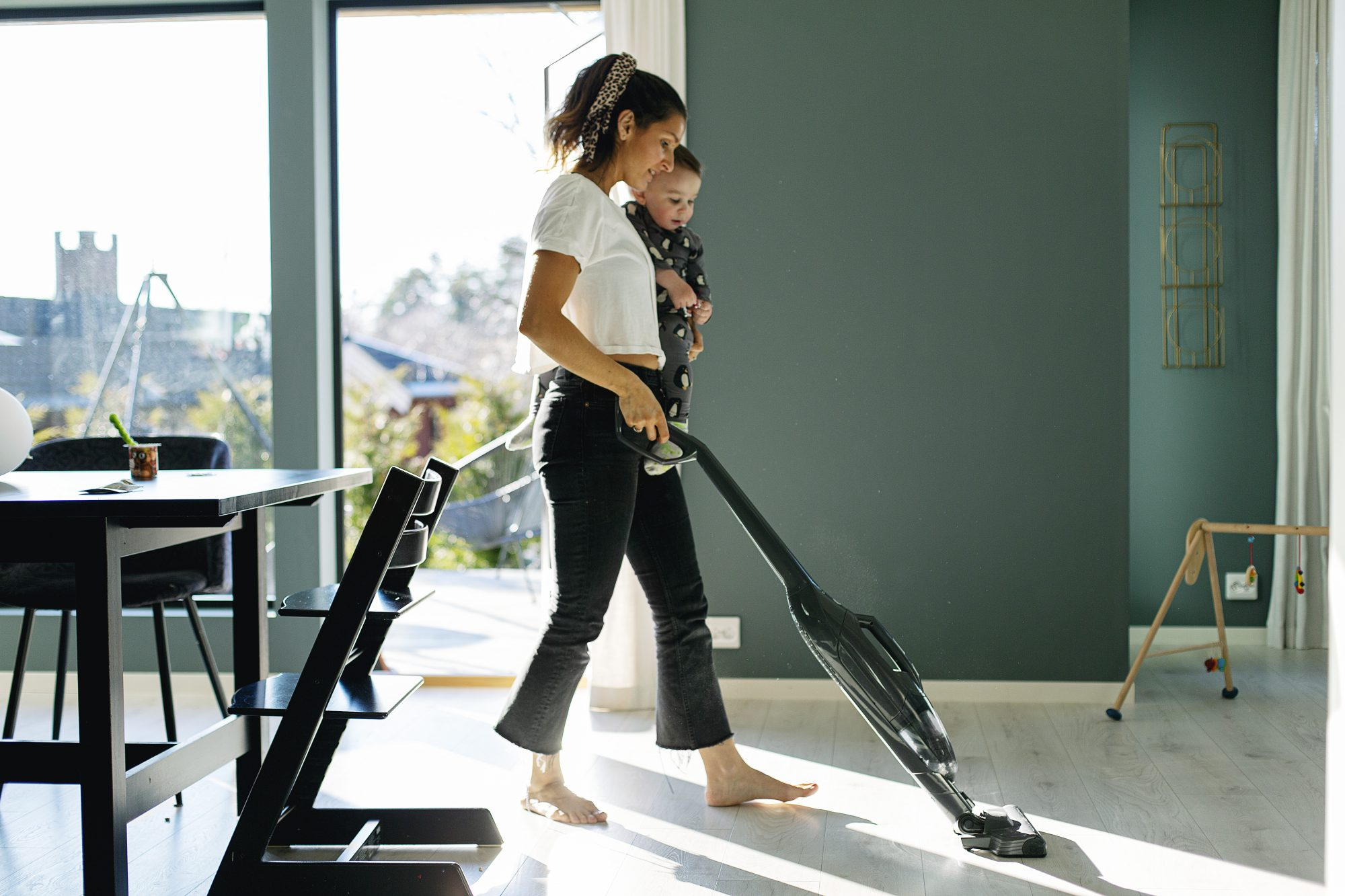 Mother vacuum cleaning while carrying toddler son