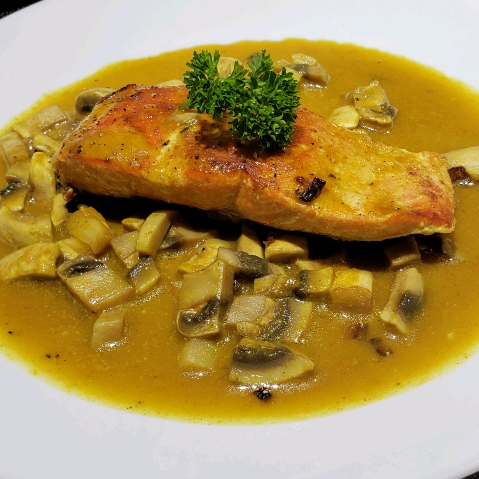 salmon with mustard colored sauce and mushrooms