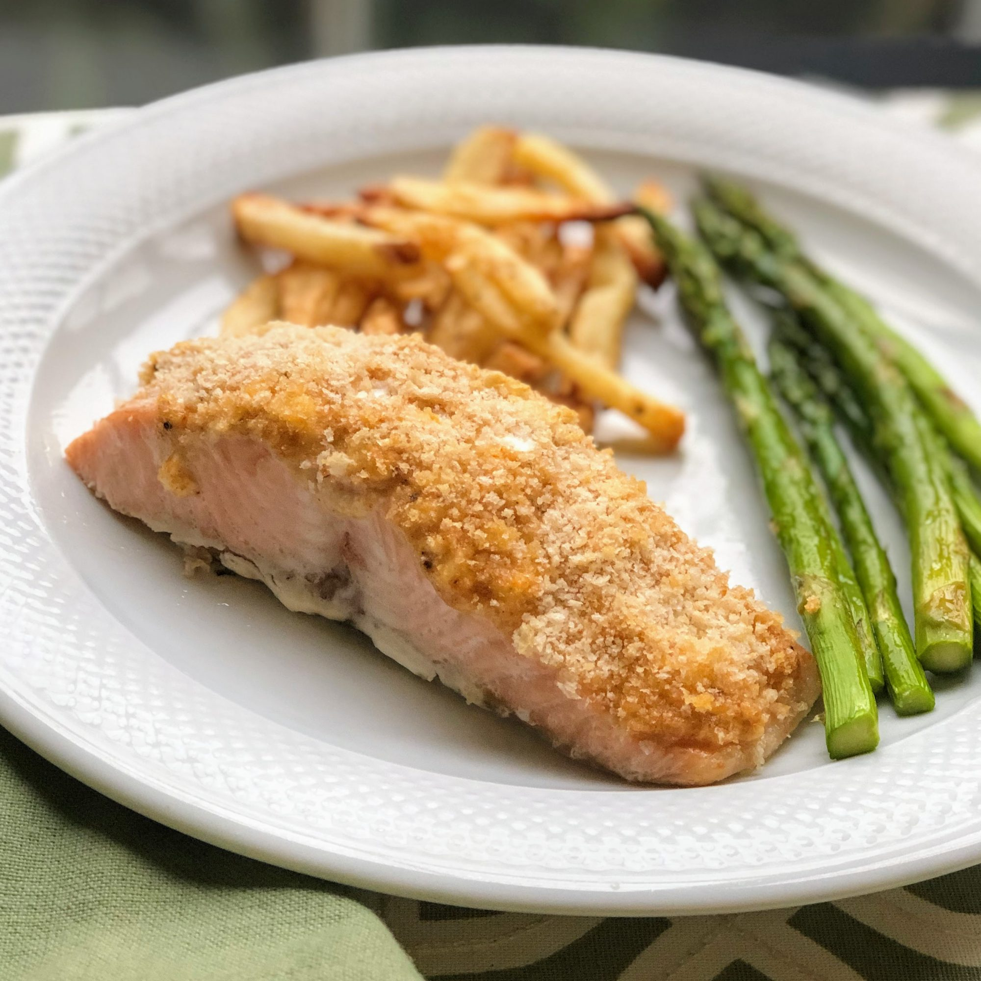 salmon fillet with bread topping and asparagus and fries on the side