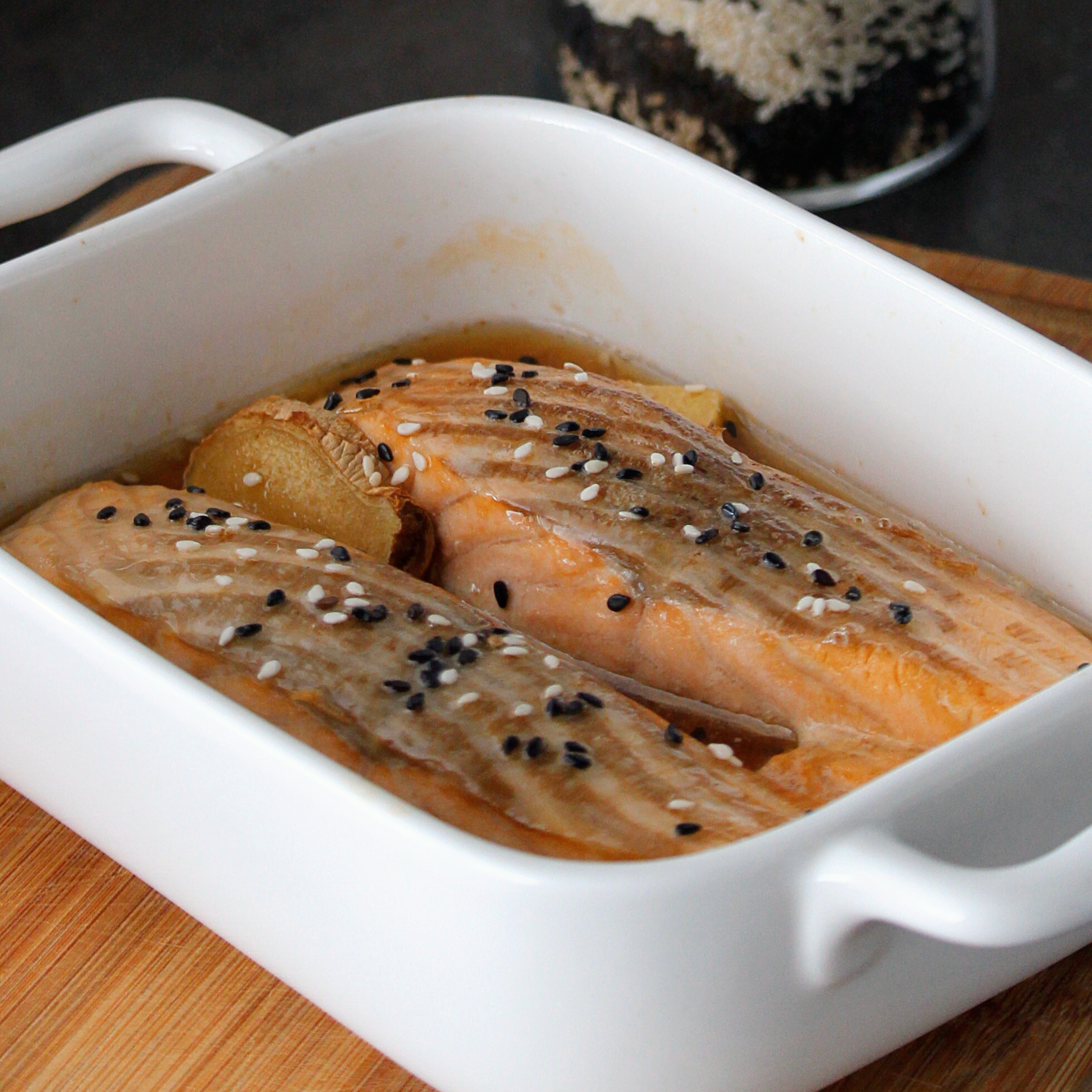 salmon fillets in casserole dish with soy sauce and ginger