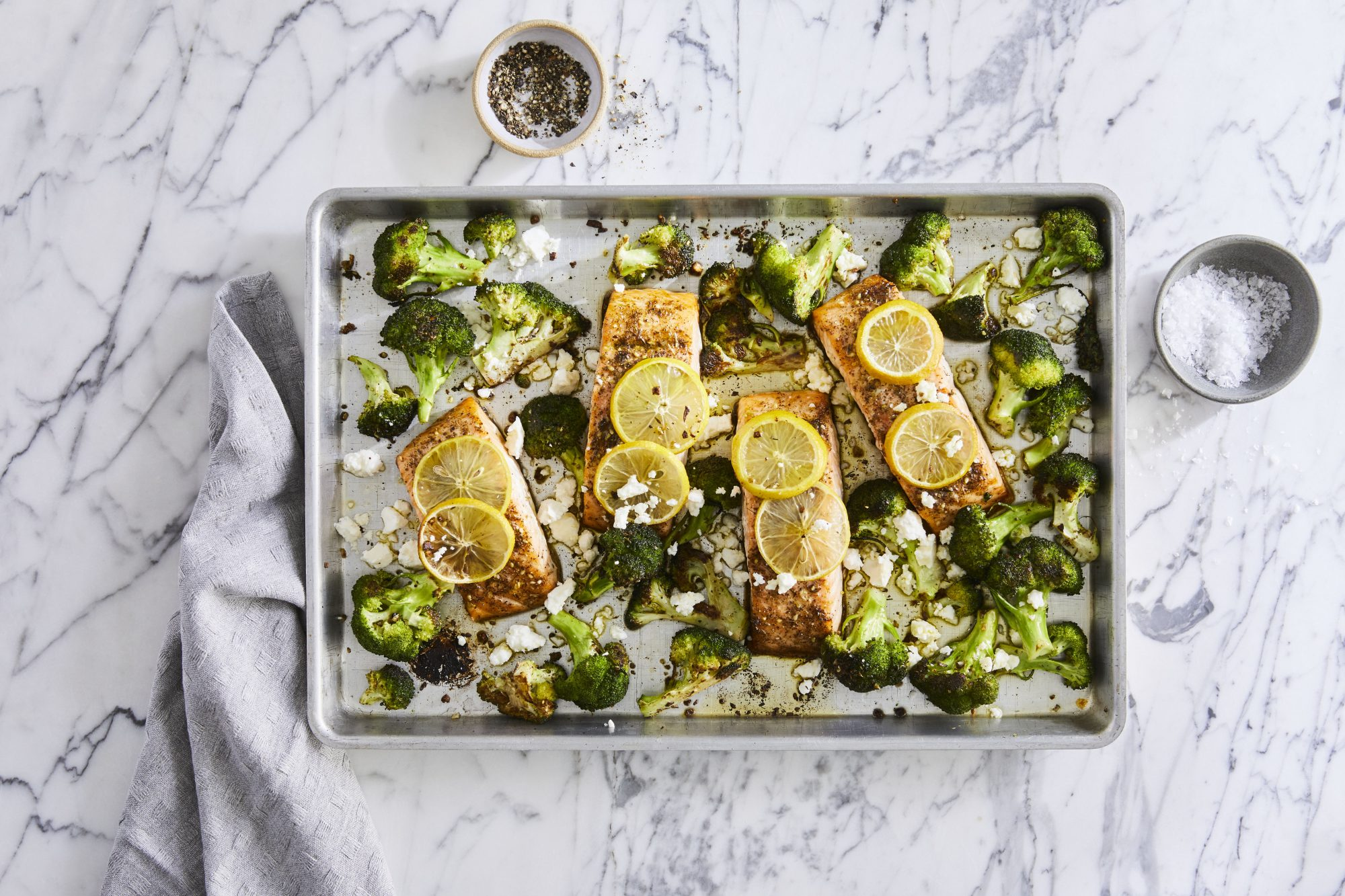 salmon filets on baking sheet with broccoli and lemon and cheese