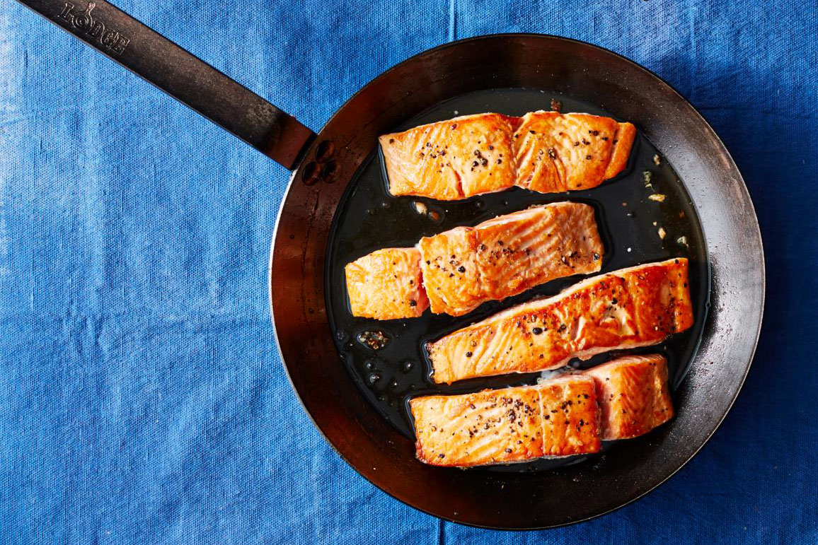 four salmon filets in carbon steel pan on a blue fabric background
