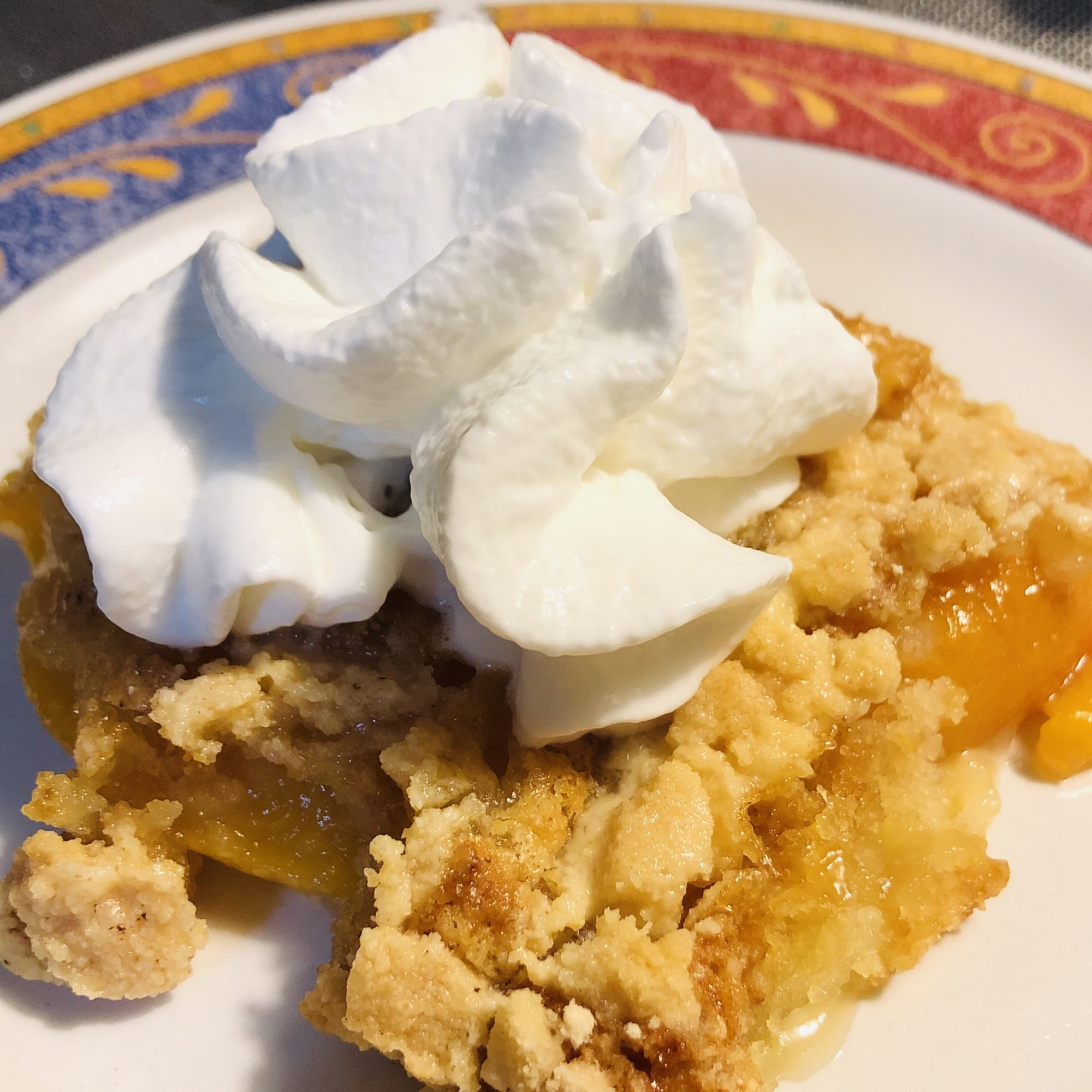a plate with peach dump cake and whipped cream