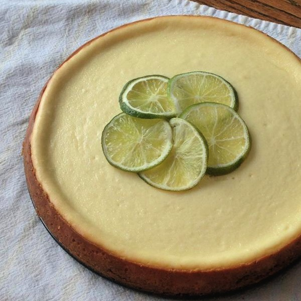 close up of key lime cheesecake garnished with slices of fresh key limes
