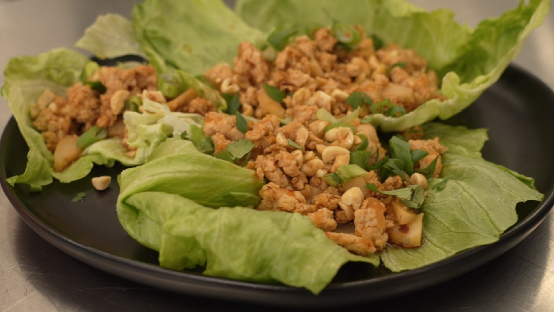 ground chicken and peanuts served on lettuce leaves