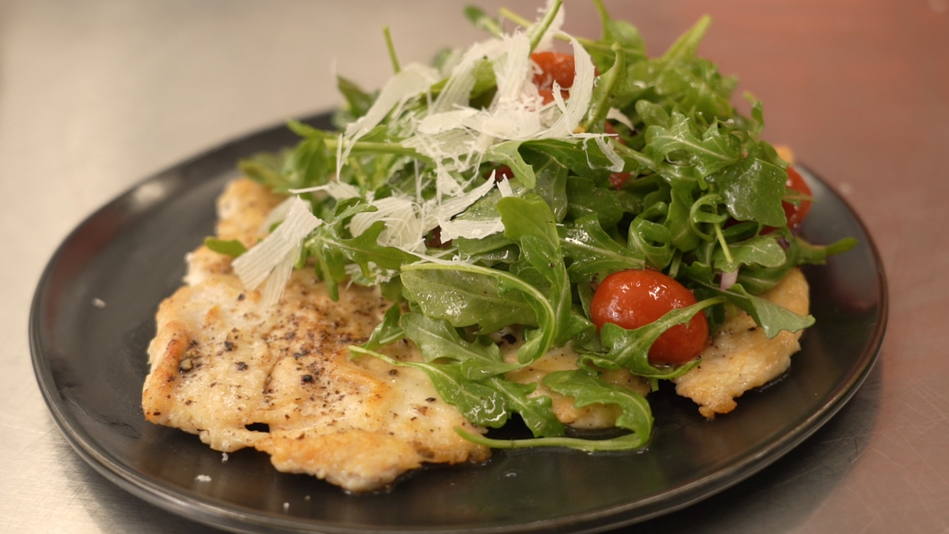 pan fried chicken breast paillard served with arugula and tomato salad topped with shaved Parmesan cheese
