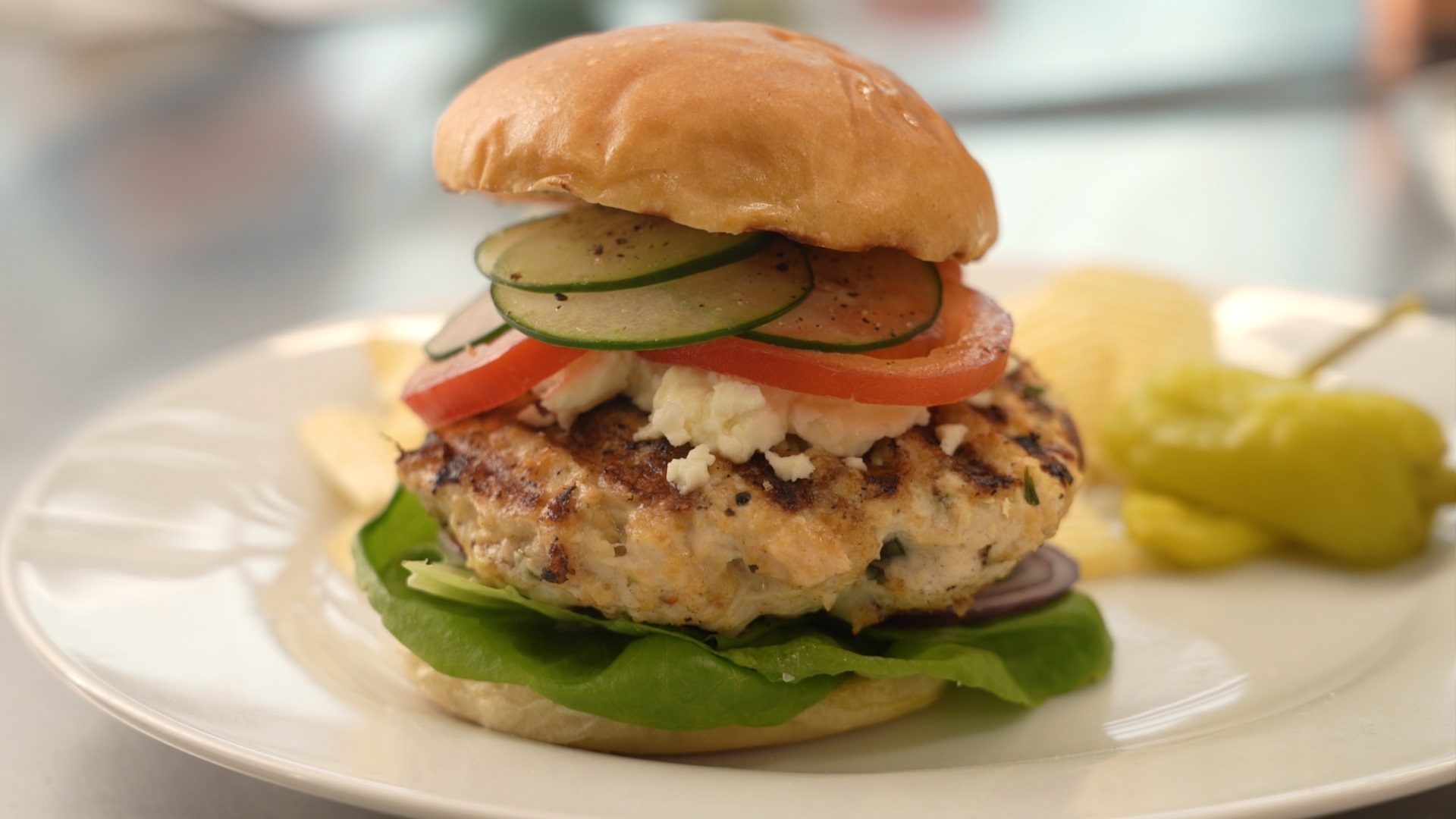 side view of a chicken burger stacked with lettuce, tomato, cucumber, and feta cheese