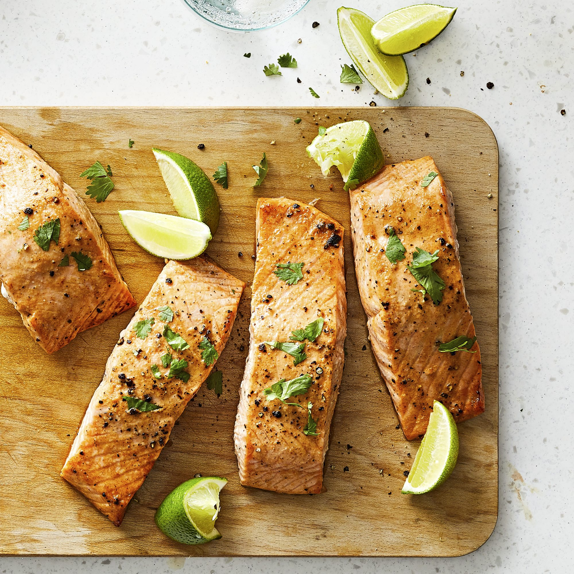 Four Lime-Marinated Baked Salmon Filets sitting on a wooden cutting board with fresh lime wedges.