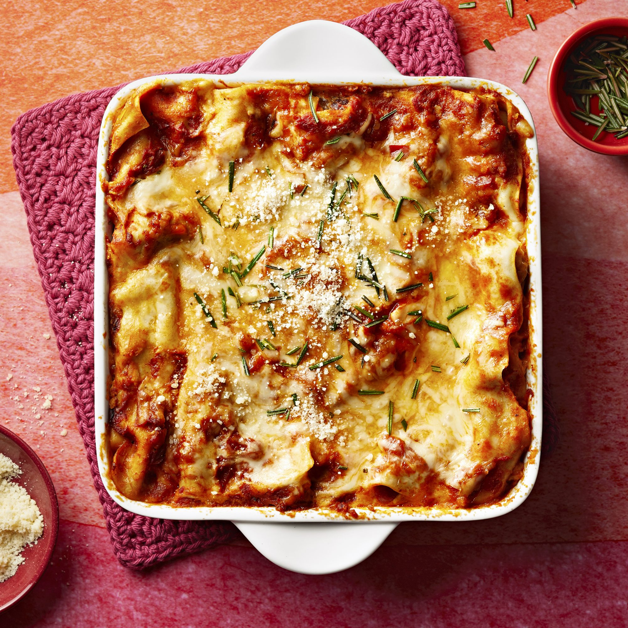 A square white casserole dish filled with Italian Sausage and Mushroom Lasagna with Bechamel Sauce
