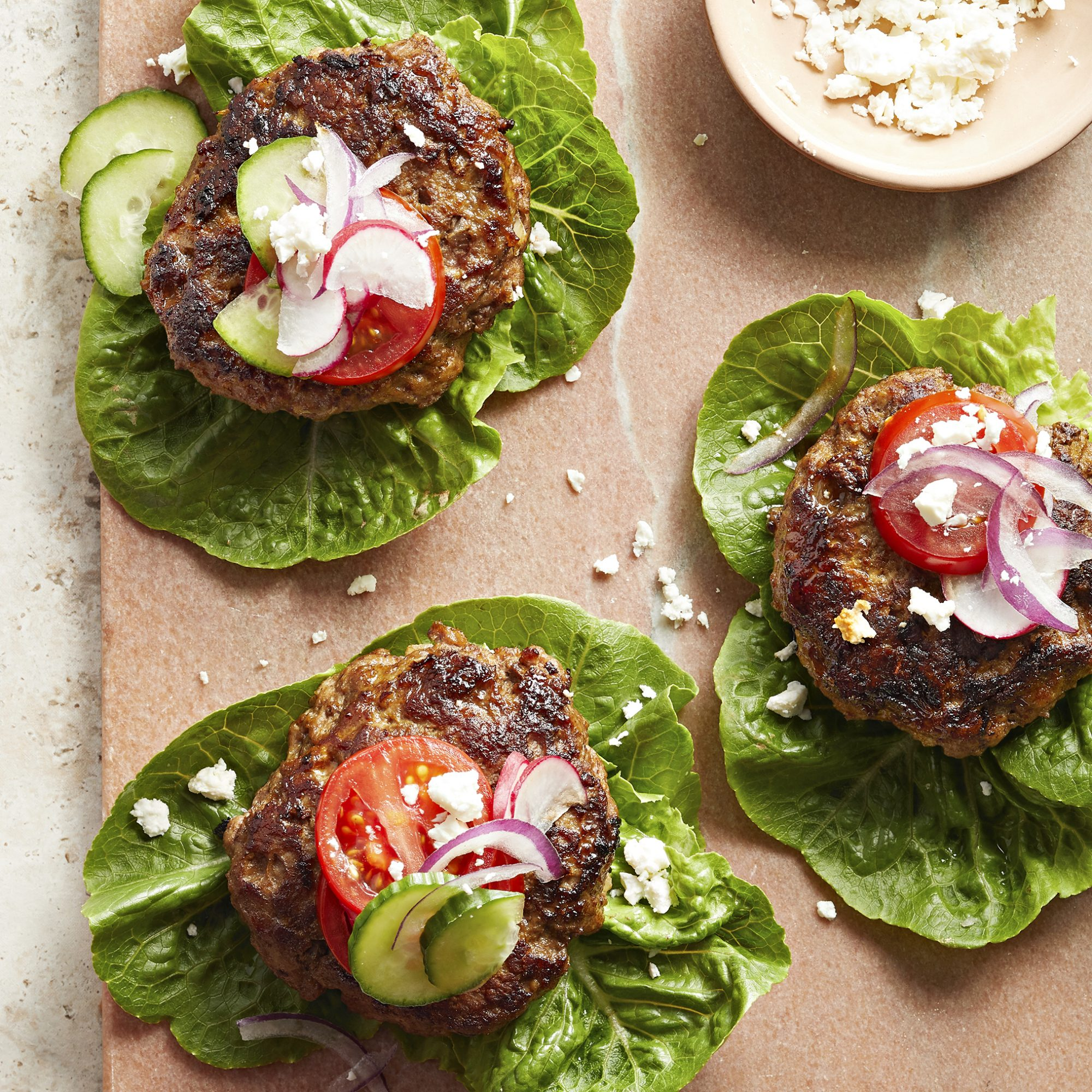 Three low carb lamb burgers-lamb burger patties served on top of leaf lettuce and served with red onion, tomato, pickles and feta cheese