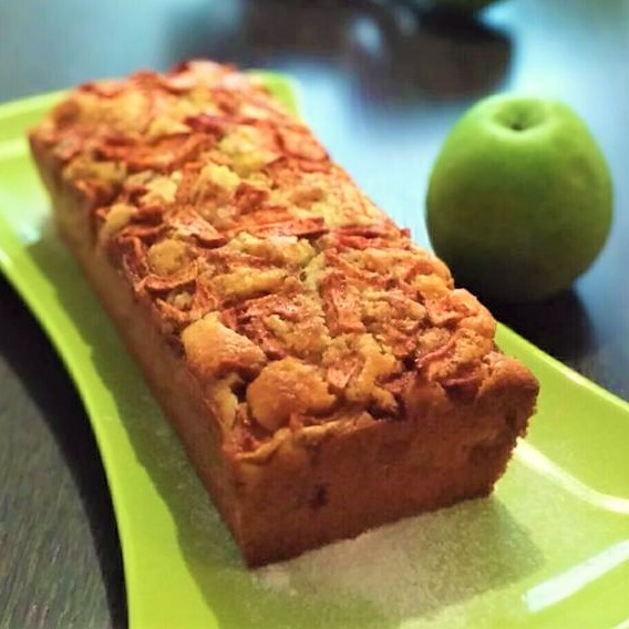 a loaf cake made with apples and cinnamon on a green plate with a green apple in the background