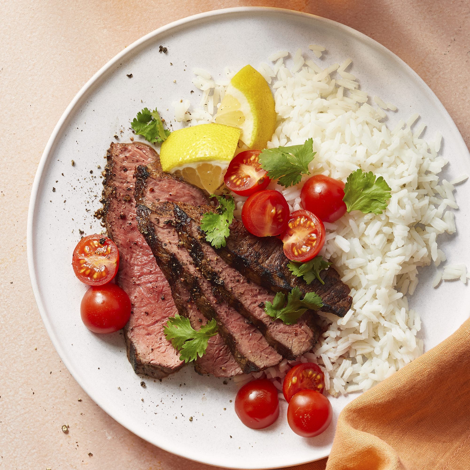 A plate of sliced Churrascaria-Style Picanha served with white rice and cherry tomatoes