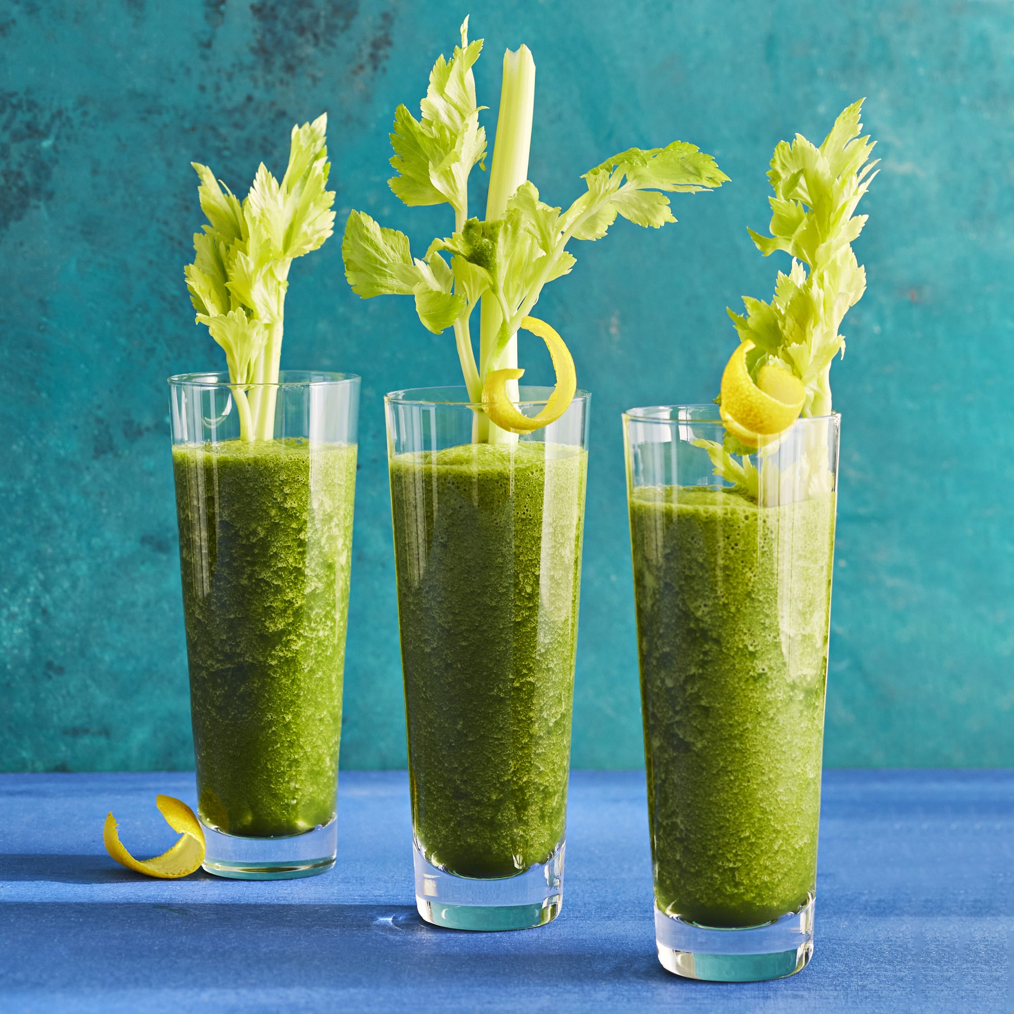 Three tall highball glasses filled with a midwinter green tonic. garnished with a stick of celery and lemon twist