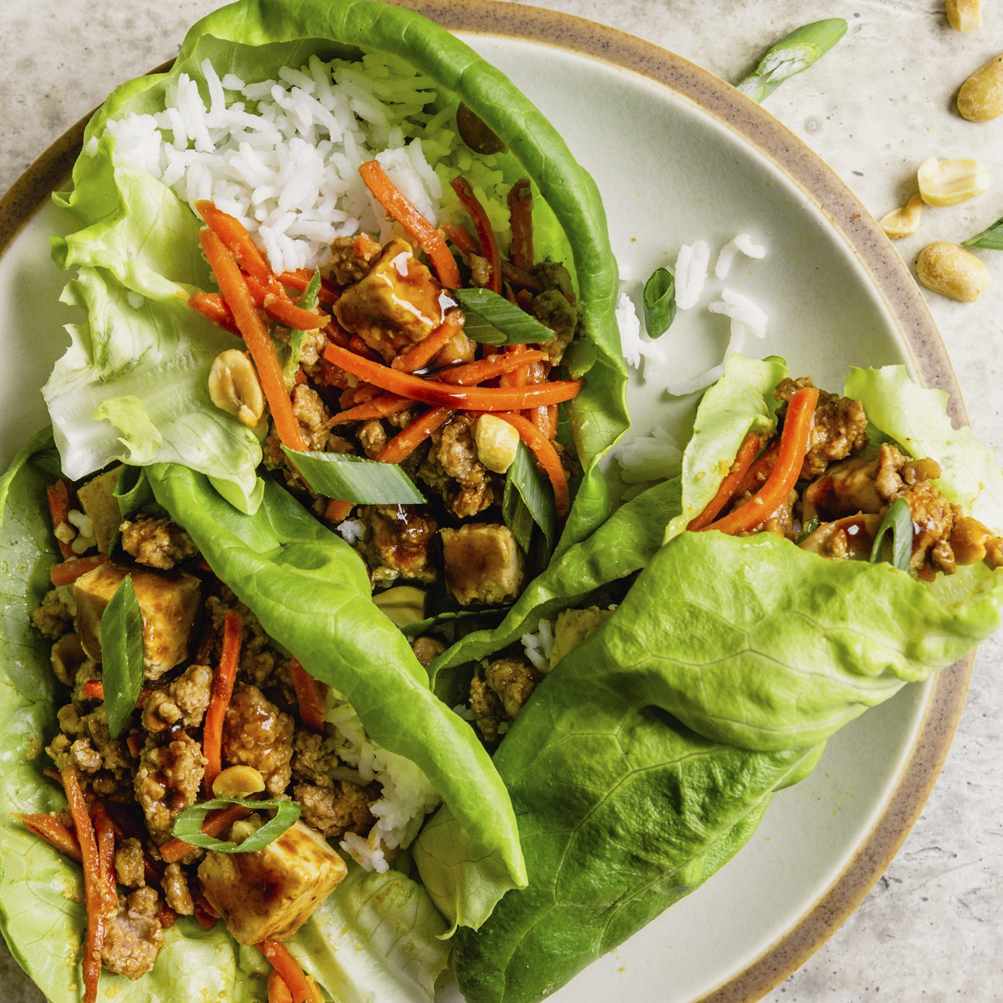 A plate of three Quick Asian Lettuce Wraps garnished with peanuts and sliced scallions