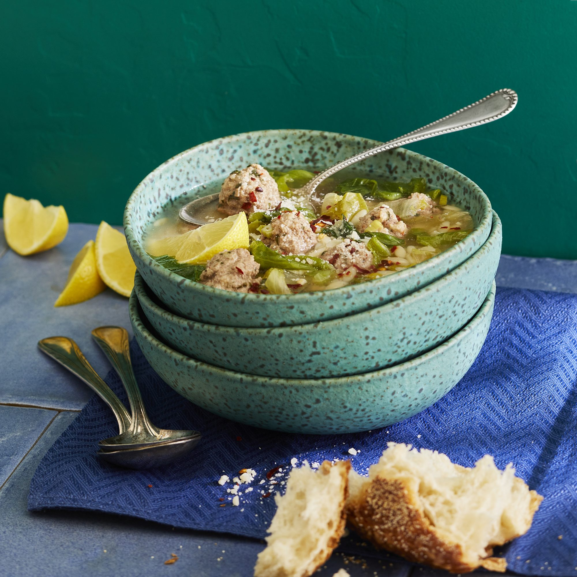 A bowl of California Italian Wedding Soup served with crusty bread and fresh lemon