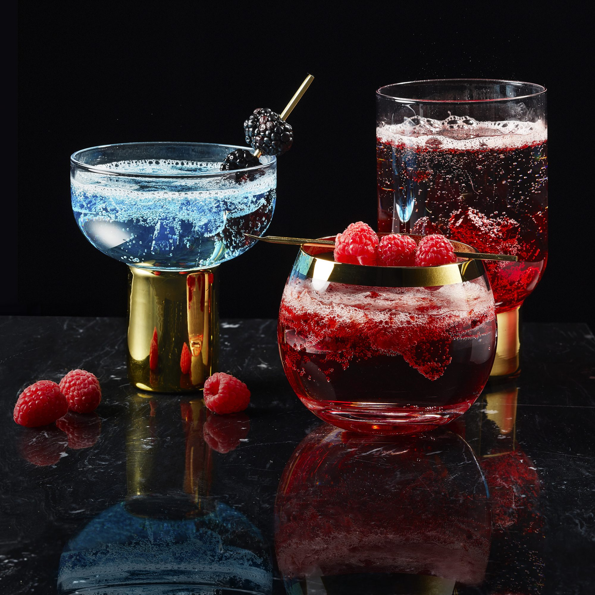 Three effervescent and colorful Lava Lamp Cocktails, garnished with fresh berries