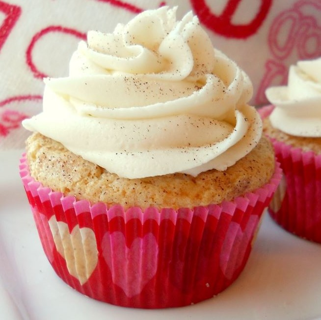 a cupcake with pink heart liner and white frosting