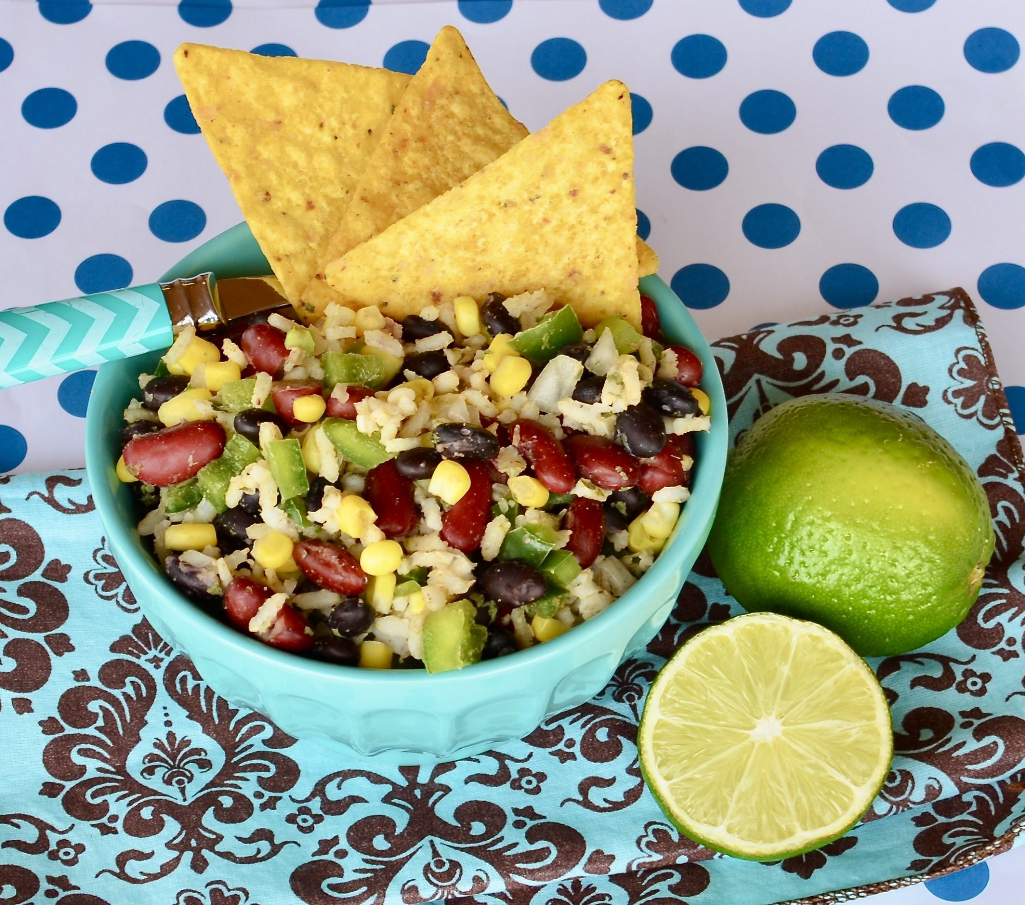 rice, bean, and corn salad in blue bowl with chips and limes