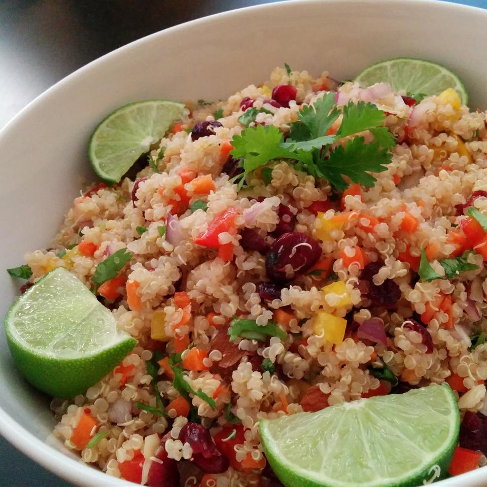 quinoa with cranberries, carrots, bell peppers, and lime wedges