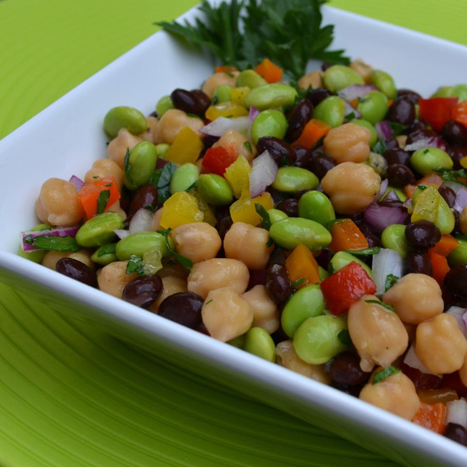 black beans, edamame, chickpeas, and peppers tossed in dressing and served in white bowl