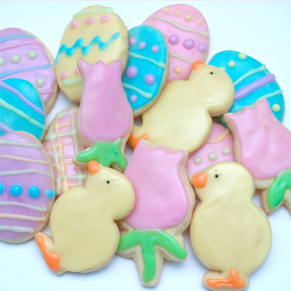 pastel-decorated cookies shaped like Easter eggs, pink tulips, and yellow baby chicks