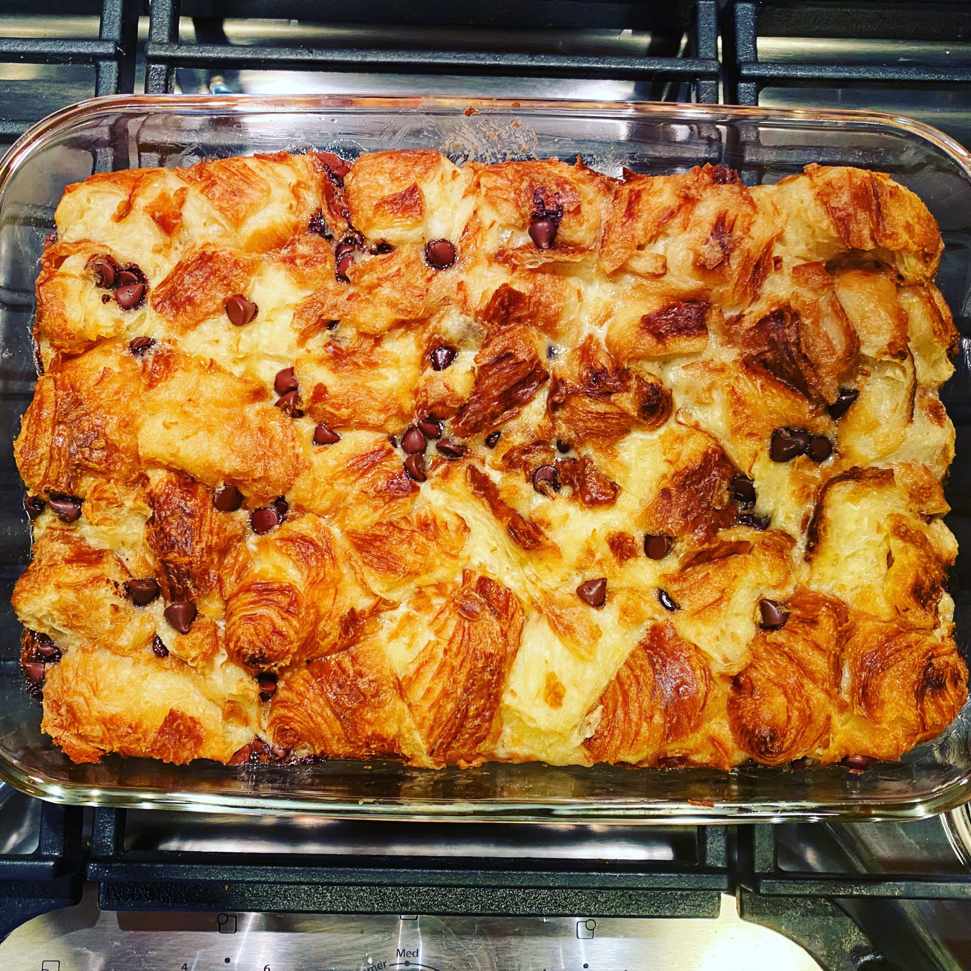 overhead shot of chocolate croissant bread pudding in a glass baking dish