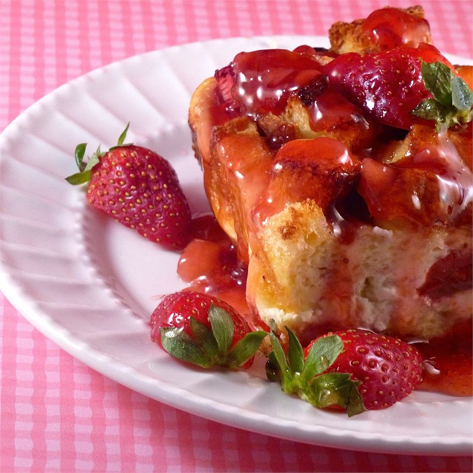 square of strawberry cream cheese casserole on a plate with fresh strawberries and strawberry sauce