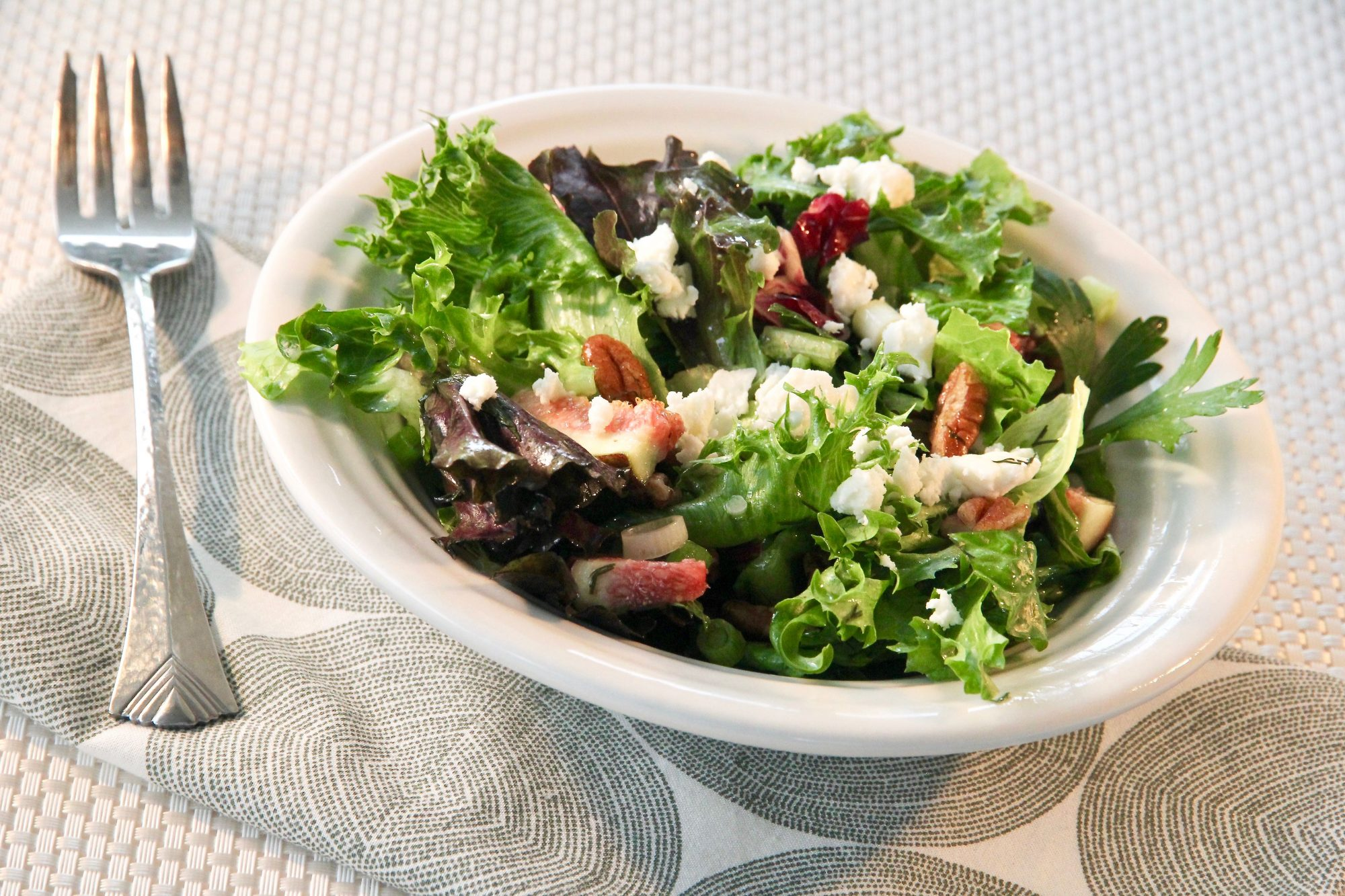 mixed greens with figs, nuts, and cheese in a bowl