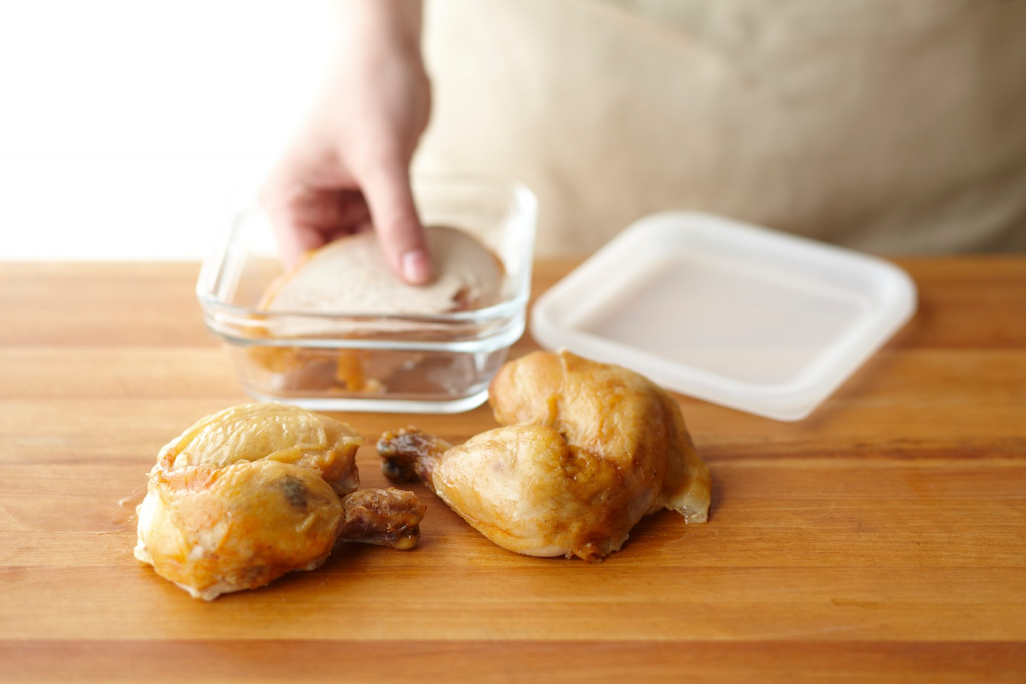 person placing cooked chicken in glass container