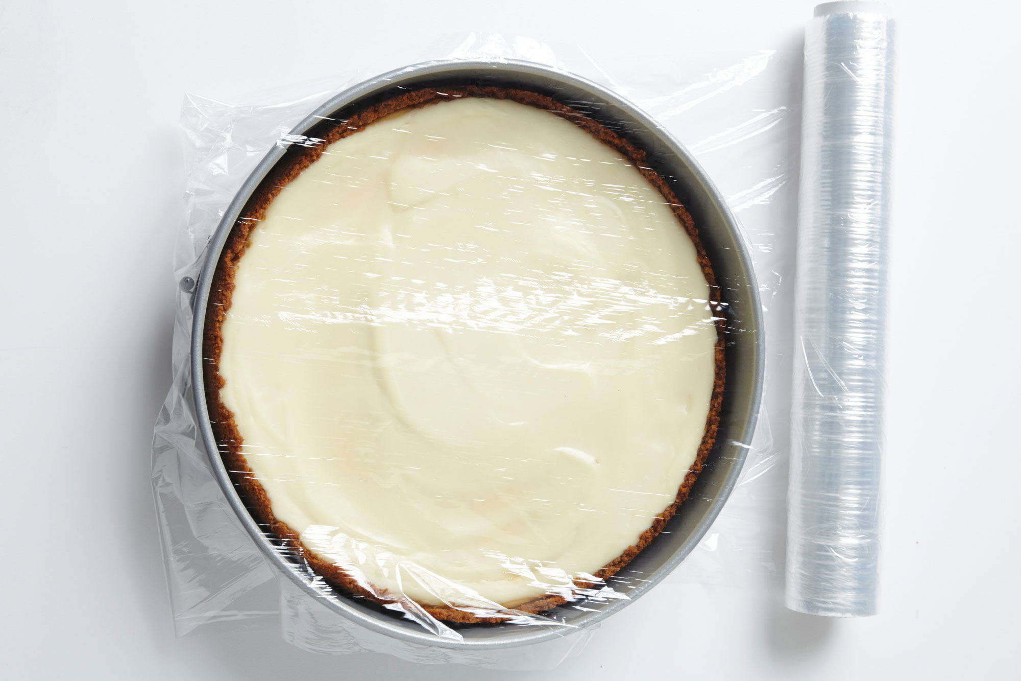 cheesecake in springform pan with plastic wrap over top