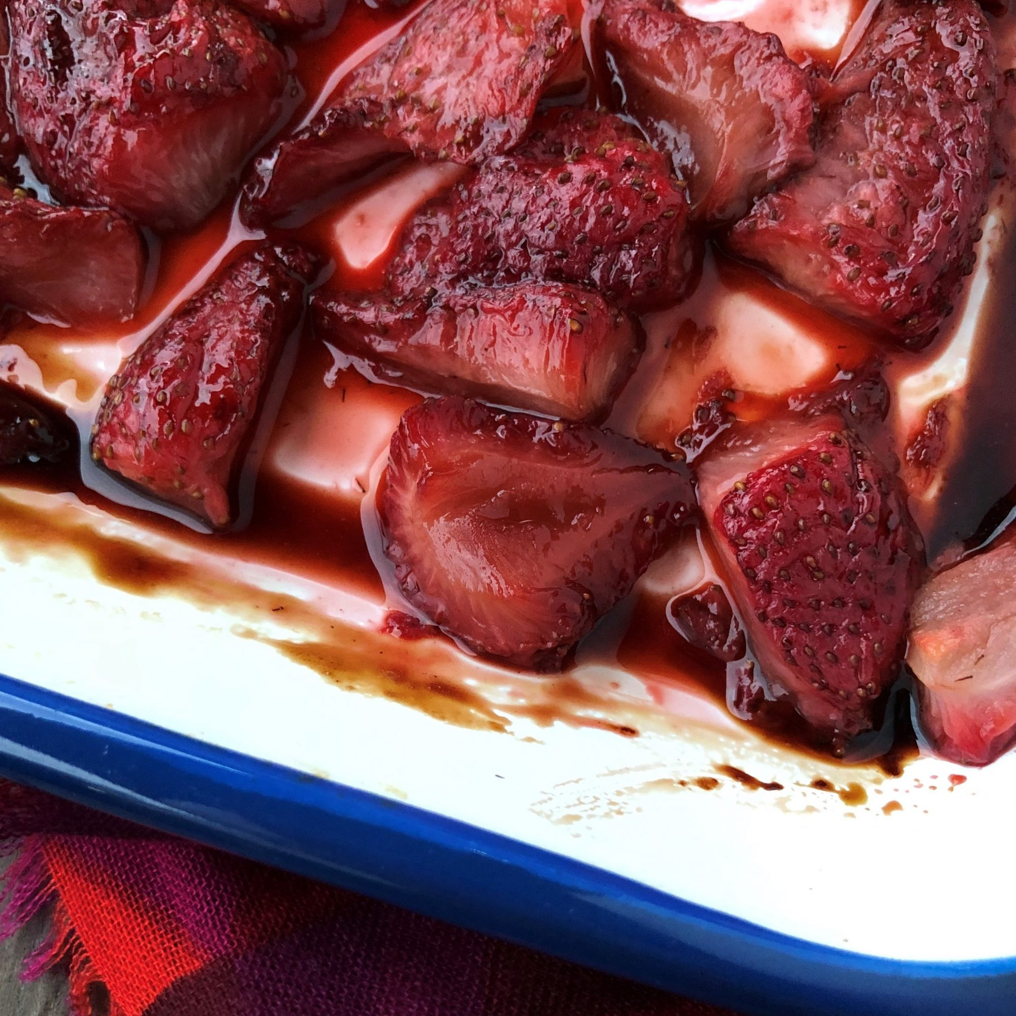 a baking dish of baked strawberries with balsamic vinegar