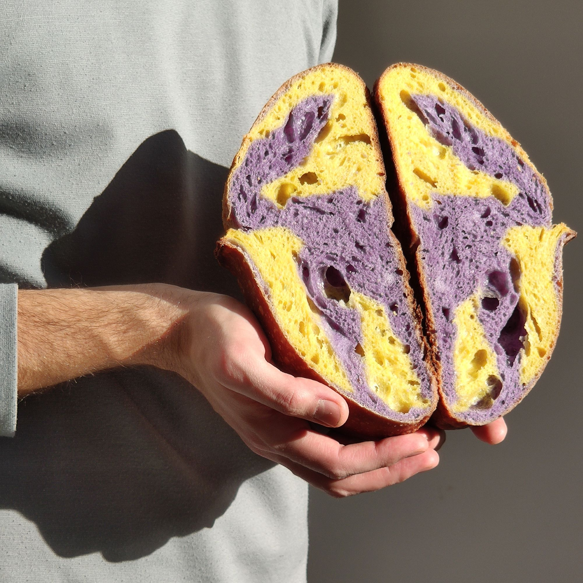man holding loaf of multicolored purple and yellow sourdough bread