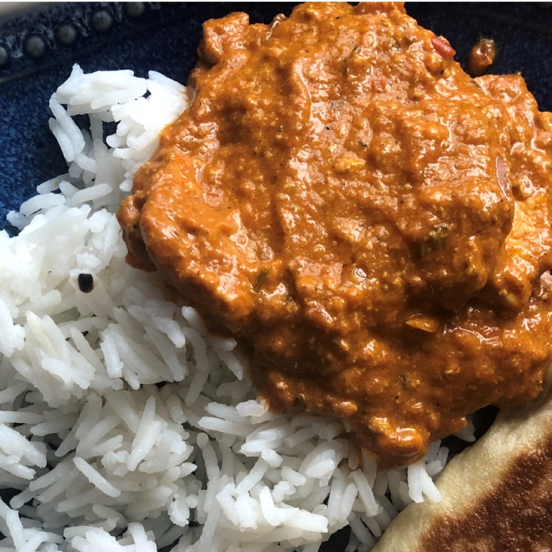 chicken tikka masala on rice with a side of naan on a blue plate